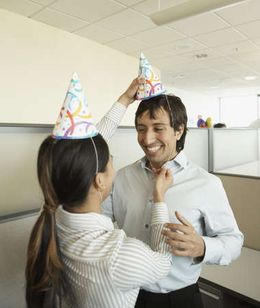 Co-workers putting on party hats at office party Stock Photo - 16090553