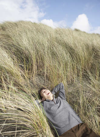 unconcerned: Asian man lying in dune grass, Ocean Beach, San Francisco, United States LANG_EVOIMAGES