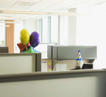office furniture: Businessman in a cubicle with a party hat on and a bunch of balloons, Redwood City, California, United States