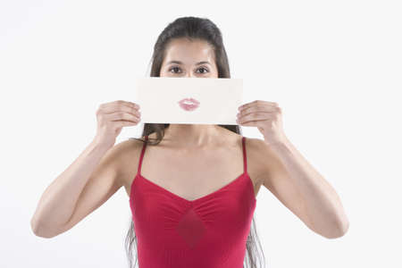 smooching: Young Hispanic woman holding a piece of paper with a lipstick imprint in front of her face LANG_EVOIMAGES