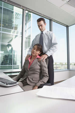 solicitous: Hispanic businessman giving Hispanic businesswoman a shoulder massage in her cubicle, Redwood City, California, United States,  LANG_EVOIMAGES