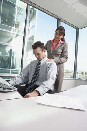Hispanic businesswoman giving Hispanic businessman a shoulder massage in his cubicle, Redwood City, California, United States,  Stock Photo - 16090591