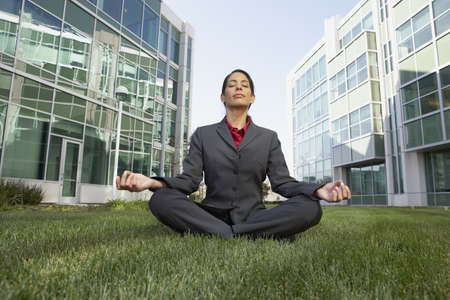 motioning: Hispanic businesswoman meditating in the grass in front of office buildings, Redwood City, California, United States LANG_EVOIMAGES