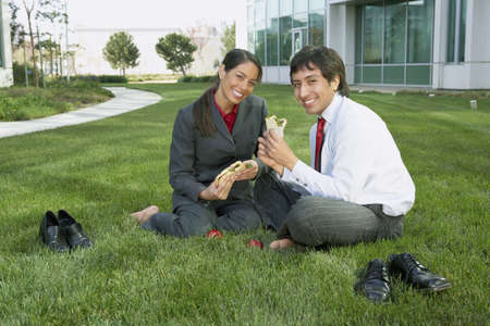 Hispanic businesswoman and businessman eating lunch in the grass, Redwood City, California, United States,  Stock Photo - 16090601