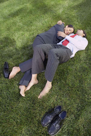 Hispanic businesswoman and businessman lying in the grass hugging, Redwood City, California, United States, Stock Photo - 16090603