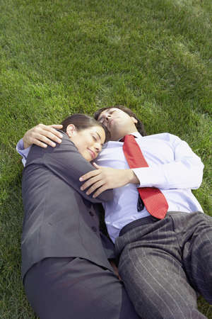 Hispanic businesswoman and businessman lying in the grass hugging, Redwood City, California, United States,  Stock Photo - 16090602