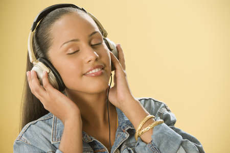 casualness: Studio shot of a Dominican woman listening to music on headphones