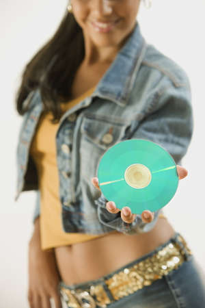 Studio shot of a young woman holding a CD Stock Photo - 16090618