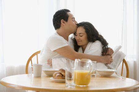 Hispanic couple hugging at the breakfast table Stock Photo - 16090637