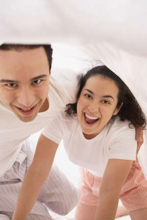 bed sheet: Hispanic couple playing under the sheet on the bed