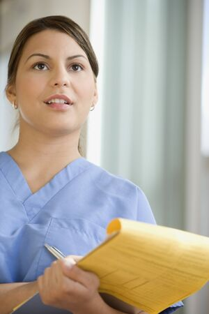 giver: Hispanic female medical professional with chart LANG_EVOIMAGES