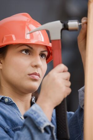 female construction worker: Hispanic female construction worker hammering a nail