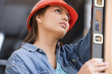 female construction worker: Hispanic female construction worker using a level