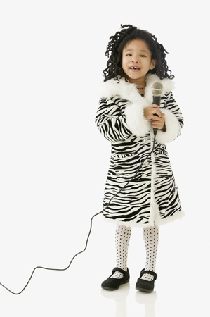 Studio shot of young African girl singing with a microphone Stock Photo - 16090665