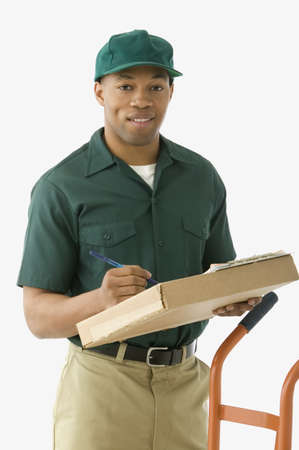 deliveryman: Studio shot of African delivery man with package and handtruck