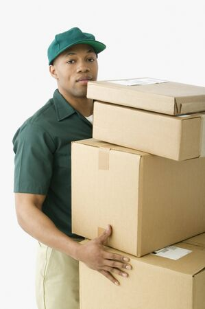piling: Studio shot of African delivery man with boxes