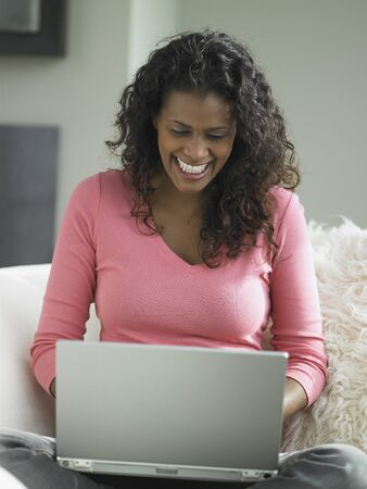 jamaican ethnicity: African woman using laptop on sofa, Toronto, Canada LANG_EVOIMAGES