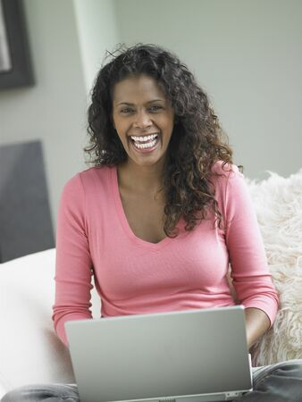 African woman using laptop on sofa, Toronto, Canada Stock Photo - 16090684