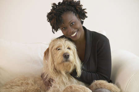 Young African woman with Labradoodle on sofa