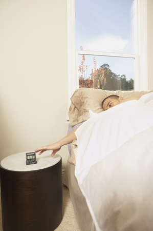 rousing: Man turning off a travel alarm clock from bed, San Rafael, California, United States LANG_EVOIMAGES