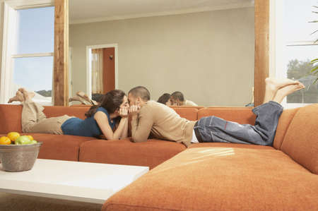 love seat: Young Hispanic couple lying on the sofa kissing, San Rafael, California, United States LANG_EVOIMAGES
