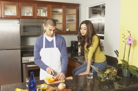 Young Hispanic couple chopping vegetables, San Rafael, California, United States
