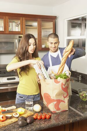 Young Hispanic couple unpacking grocery bag, San Rafael, California, United States Stock Photo - 16070340