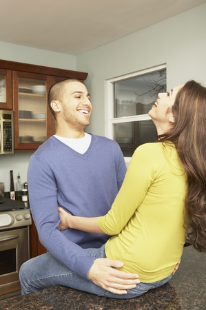 Young Hispanic couple hugging in the kitchen, San Rafael, California, United States