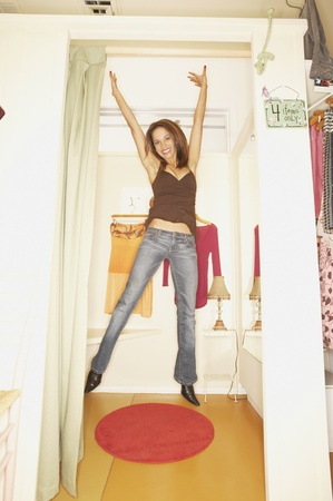 Woman jumping in a fitting room, Larkspur, California, United States