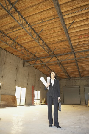 empty warehouse: Businesswoman standing in empty warehouse with blueprints, San Rafael, California, United States
