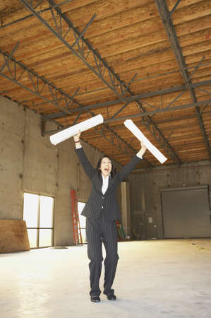 Businesswoman cheering in empty warehouse with blueprints, San Rafael, California, United States