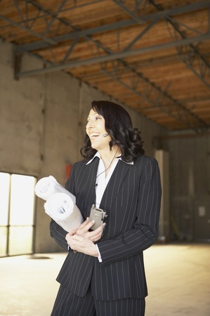hands free device: Businesswoman standing in empty warehouse with blueprints, San Rafael, California, United States