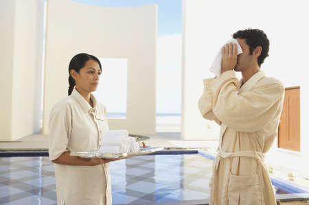 Man in robe using hot towel at hotel, Los Cabos, Mexico Stock Photo - 16090751