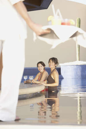 Two Hispanic women with drinks in a hotel pool, Los Cabos, Mexico Stock Photo - 16090771