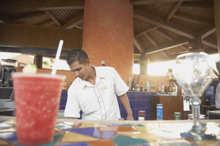 barkeep: Drinks on a bar with bartender in background, Los Cabos, Mexico