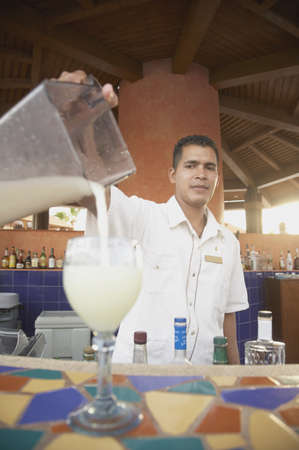 barkeep: Hispanic male bartender pouring a pina colada, Los Cabos, Mexico LANG_EVOIMAGES