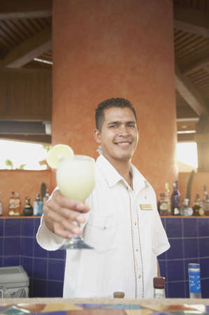 barkeep: Hispanic male bartender offering up a pina colada, Los Cabos, Mexico