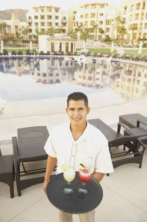pool side: Hispanic male waiter with a tray of drinks, Los Cabos, Mexico