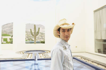 stepping: Man in cowboy hat standing next to a hotel pool, Los Cabos, Mexico