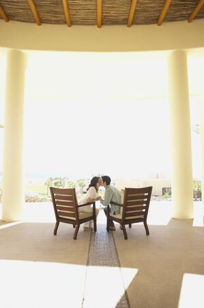 longshot: Couple kissing on patio at hotel, Los Cabos, Mexico