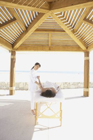 Woman getting massage outdoors at health spa, Los Cabos, Mexico