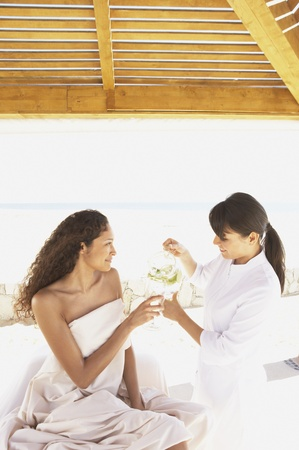 Spa employee pouring a glass of water for woman sitting on massage table, Los Cabos, Mexico Stock Photo