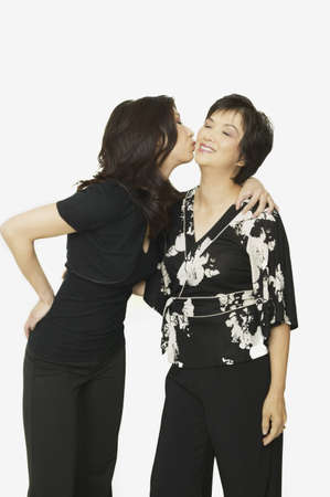 attentiveness: Studio shot of adult Asian daughter kissing mother on cheek