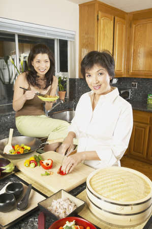 Asian mother and adult daughter in the kitchen with food