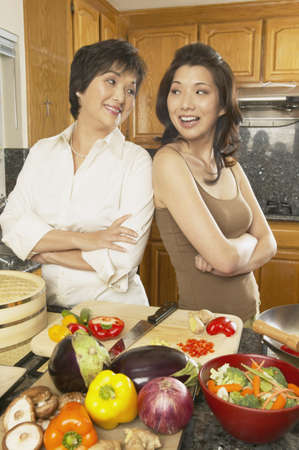 two person only: Asian mother and grown daughter preparing dinner, Freemont, California, United States LANG_EVOIMAGES