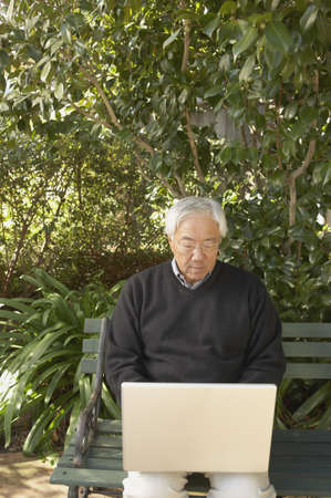 Senior Asian man with laptop sitting on a park bench, San Rafael, California, United States Stock Photo - 16090862