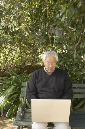 Senior Asian man with laptop sitting on a park bench, San Rafael, California, United States Stock Photo - 16090862