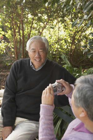 Senior Asian man having his photograph taken on a park bench, San Rafael, California, United States Stock Photo - 16090863