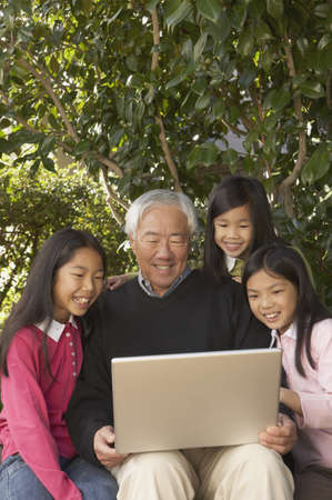 Asian grandfather with granddaughters and laptop, San Rafael, California, United States Stock Photo - 16090870