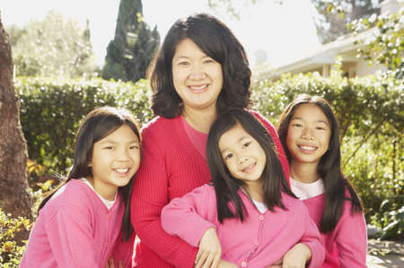 san rafael: Asian mother with three young daughters smiling outdoors, San Rafael, California, United States